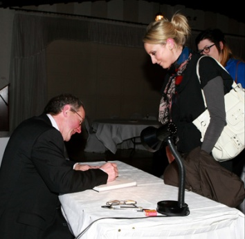 """John Hooton autographing a copy of his first book """"Gathering Light on the Dingle Coast"""""""